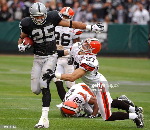 Oakland Raiders running back Justin Fargas tries to avoid a diving tackle attempt by Cleveland Browns defensive back Brian Russell on a 48yard run in...