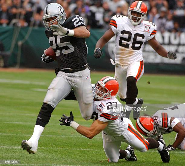 Oakland Raiders running back Justin Fargas tries to elude a diving tackle attempt by Cleveland Browns defensive back Brian Russell on a 48yard run in...