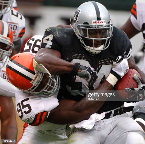 Oakland Raiders running back LaMont Jordan tries to break free from grasp of Cleveland Browns linebacker Kamerion Wimbley at McAfee Coliseum in...