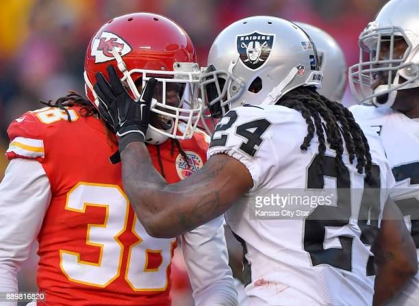 Oakland Raiders running back Marshawn Lynch pats Kansas City Chiefs free safety Ron Parker on the helmet after avoiding Parker's tackle and scoring...