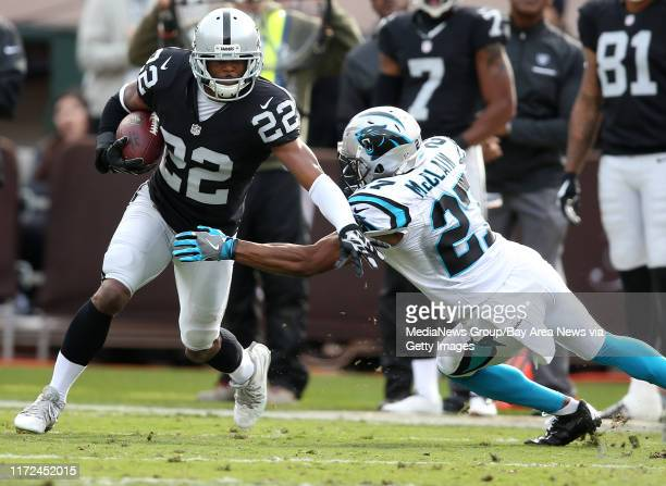 Oakland Raiders running back Taiwan Jones works to get past Carolina Panthers corner back Robert McClain during the first quarter of their game on...