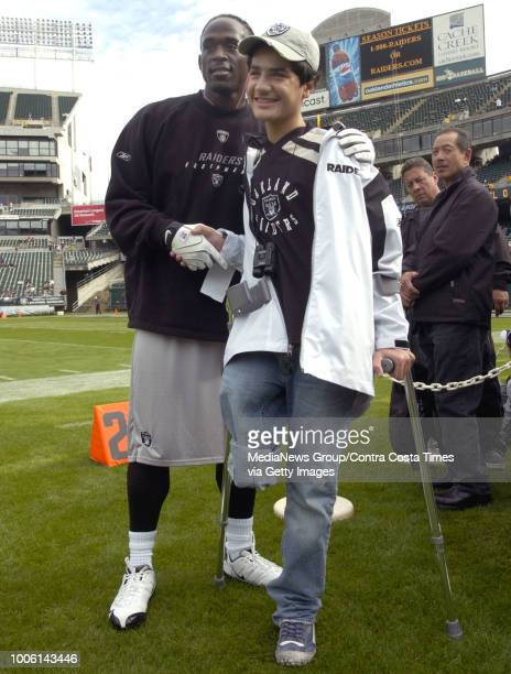 Oakland Raiders safety Hiram Eugene left welcomes Ahmed Ali aEtabbi a 14yearold from Iraq who is a big Raiders fan to the Atlanta Falcons/ Raiders...