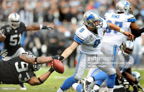 Oakland Raiders Tommy Kelly left knocks the ball from the hand of Detroit Lions quarterback Matthew Stafford causing a fumble recovery and touchdown...