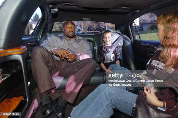 Oakland Raiders Warren Sapp shares a seat with Amanda Alfaro 10 when he picks her up to go to school at Bollinger Canyon Elementary in a large black...