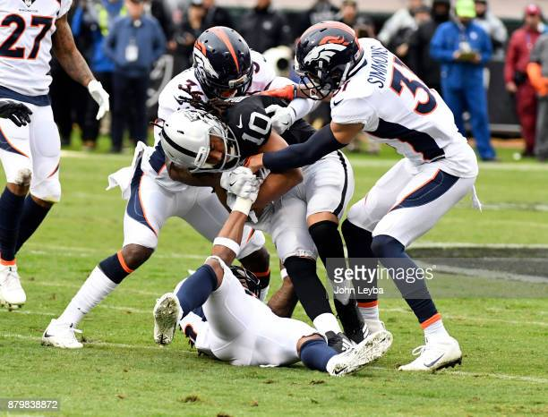 Oakland Raiders wide receiver Seth Roberts gets wrapped up by Denver Broncos defensive back Will Parks and strong safety Justin Simmons during the...
