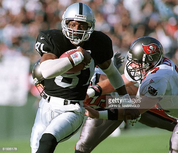Oakland Raiders wide receiver Tim Brown eludes a tackle from Tampa Bay Buccaneers safety John Lynch to score the Raiders first touchdown on a pass...