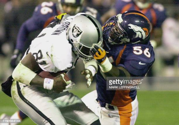 Oakland Raiders wide receiver Tim Brown gets tackled by Denver Broncos' linebacker Al Wilson after a short reception during Monday nights' game at...