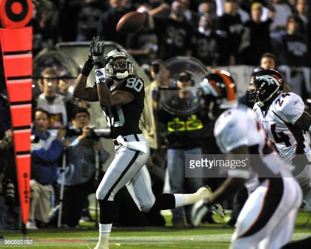 Oakland Raiders widereceiver Jerry Rice hauls in a catch from Raiders quarterback Rich Gannon as Denver Broncos cornerback Deltha O'Neal and Broncos...