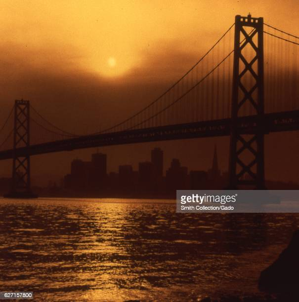 Oakland San Francisco Bay Bridge at dusk with the skyline of San Francisco California in the background 1975