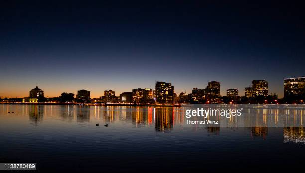 oakland skyline and lake merritt at dusk - oakland california skyline stock pictures, royalty-free photos & images