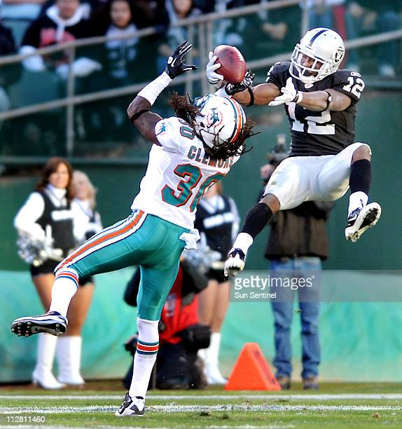 Oakland's Jacoby Ford makes a catch against defensive pressure from Miami's Chris Clemons in the fourth quarter of an NFL game at the OaklandAlameda...