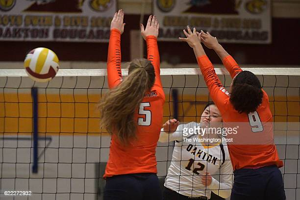 Oakton Cougars Alice Yang spikes the ball past West Springfield Spartans Hailey Olsen and West Springfield Spartans Kyla Harris in the first game...