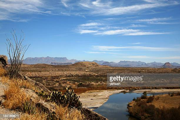 Oasis at the edge of a desert with mountain range from afar
