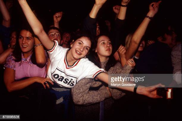 Oasis fans wearing band tshirts in the front rows of the crowd watching them perform at at Earls Court London November 1995
