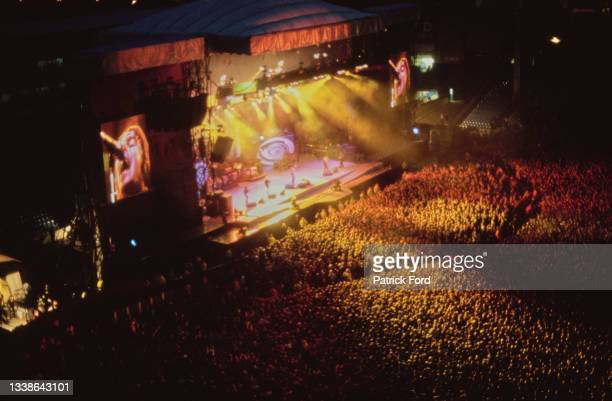 Oasis performs on stage in front of a large crowd at an unspecified event, UK, circa 1996.