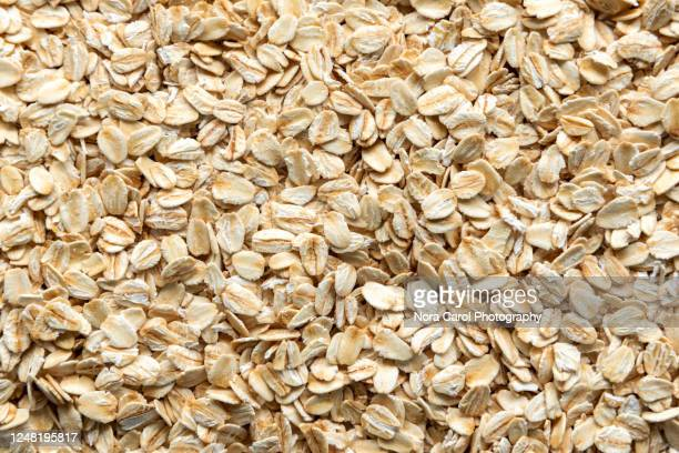 oat flakes background - oatmeal stock pictures, royalty-free photos & images