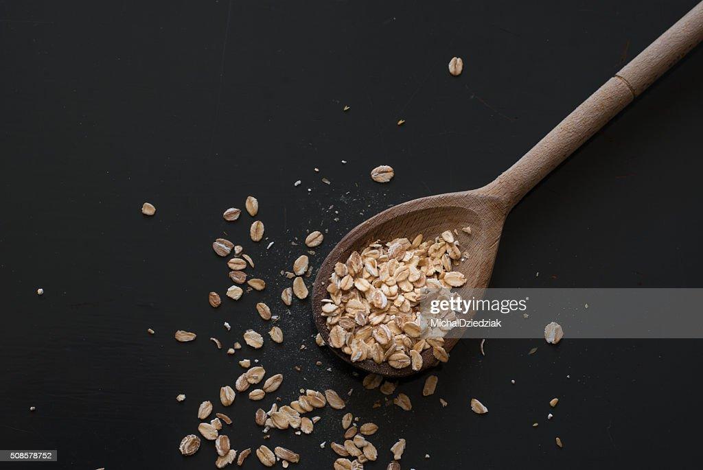 oat flakes on wooden spoon on dark wooden table : Stock Photo