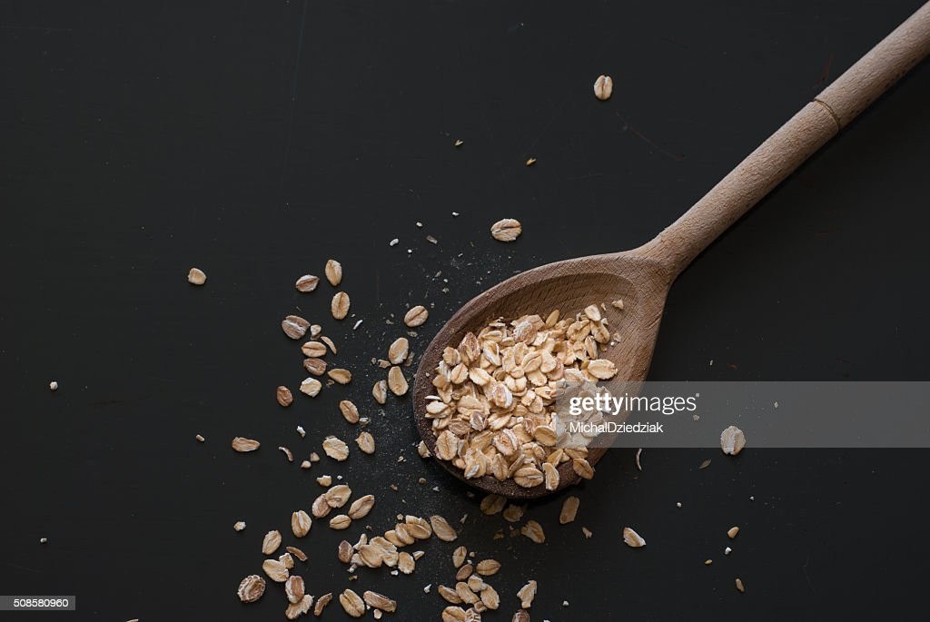 oat flakes on wooden spoon on dark wooden table : Stockfoto