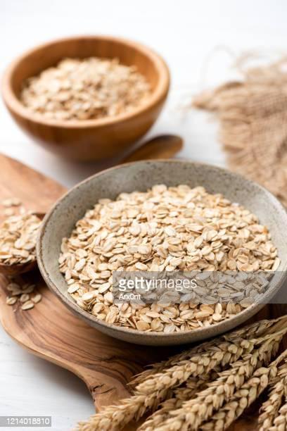 oat flakes, rolled oats in bowl - céréale photos et images de collection