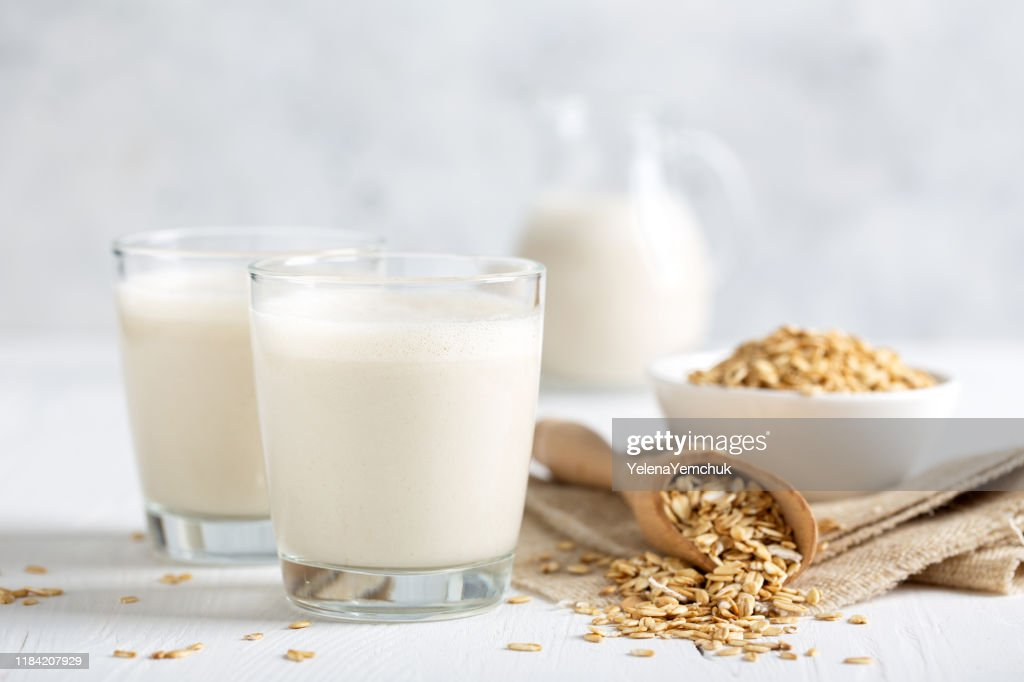Oat milk. Healthy vegan non-dairy organic drink with flakes : Stock Photo