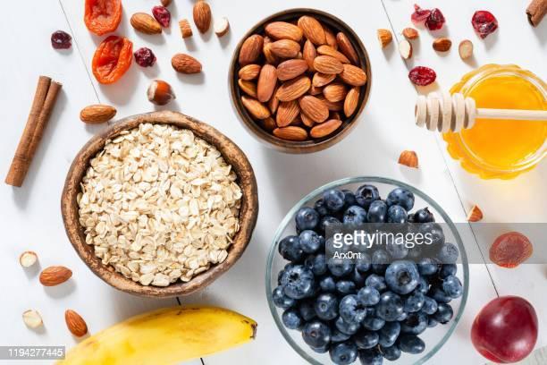 oatmeal, blueberries, almonds and honey for cooking breakfast porridge - ポリッジ ストックフォトと画像