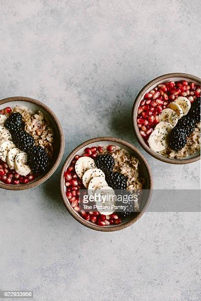 3 oatmeal bowls topped off with blackberry, banana, and pomegranate seeds are photographed from the top view.