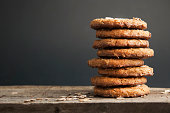 Oatmeal cookies or biscuits with oats, nuts, eggs and flour on brown dark woodenboard with black background, side view.