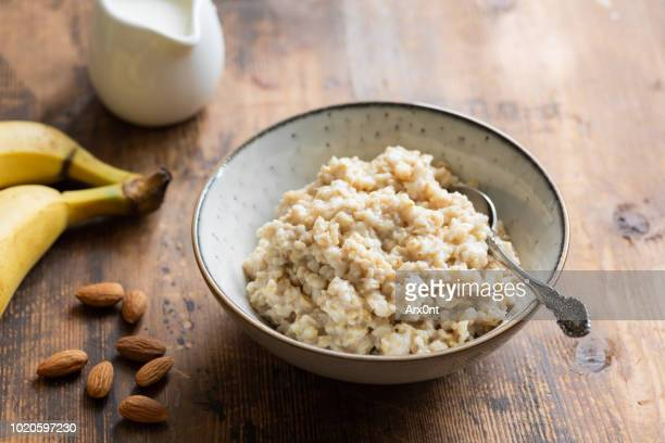 oatmeal porridge in bowl for healthy breakfast - oatmeal stock pictures, royalty-free photos & images