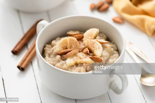 oatmeal porridge with almonds, banana and cinnamon - ポリッジ ストックフォトと画像