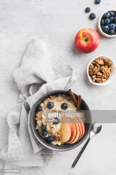oatmeal porridge with apple and cinnamon - oatmeal stock pictures, royalty-free photos & images