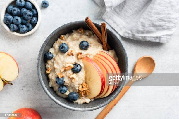oatmeal porridge with apple, cinnamon and blueberries - oatmeal stock pictures, royalty-free photos & images