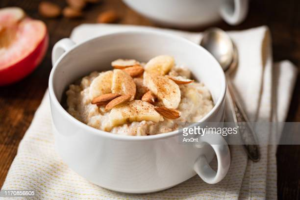 oatmeal porridge with banana, cinnamon and almonds - oatmeal stock pictures, royalty-free photos & images