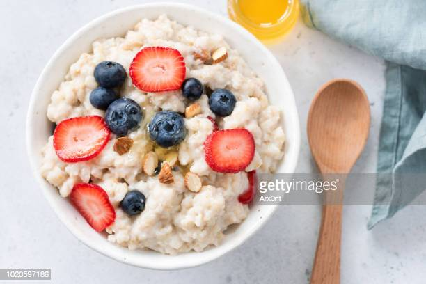 oatmeal porridge with berries and almonds in bowl, top view - oatmeal stock pictures, royalty-free photos & images
