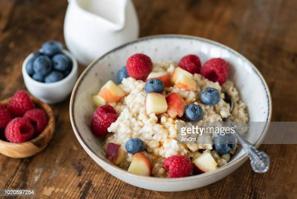oatmeal porridge with berries and honey on wooden table - oatmeal stock pictures, royalty-free photos & images