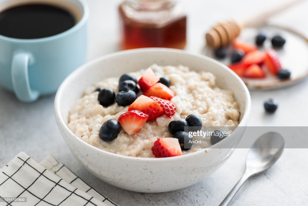 Oatmeal porridge with berries, honey and cup of coffee : Stock Photo