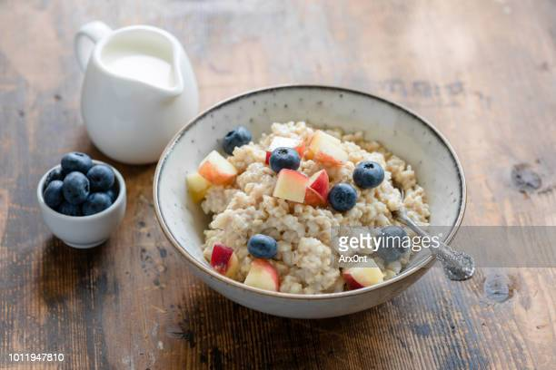 oatmeal porridge with blueberries and peach - oatmeal stock pictures, royalty-free photos & images
