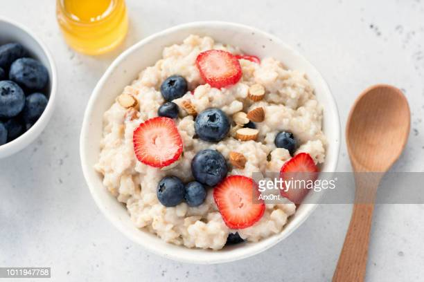 oatmeal porridge with fresh berries in a bowl - oatmeal stock pictures, royalty-free photos & images