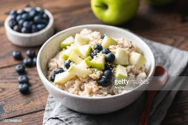 oatmeal porridge with green apple and blueberries - oatmeal stock pictures, royalty-free photos & images