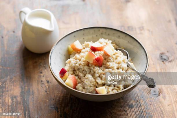 oatmeal porridge with peach in bowl - rolled oats stock photos and pictures