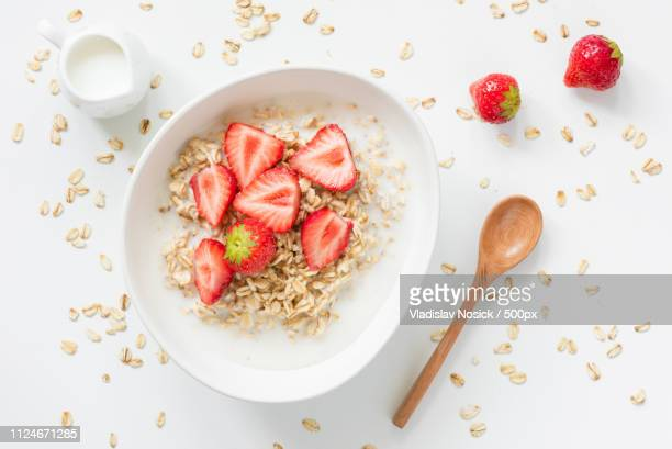 oatmeal porridge with strawberries and milk in bowl - rolled oats stock photos and pictures