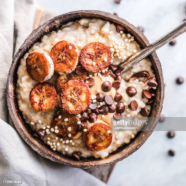 oatmeal with caramelized banana, nut butter, chocolate chips and puffed quinoa - ポリッジ ストックフォトと画像