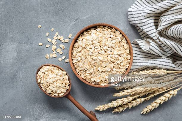 oats, rolled oats or oat flakes in wooden bowl - oatmeal stock pictures, royalty-free photos & images