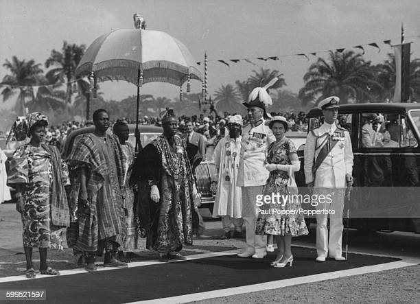 Oba Adeniji Adele II King of Lagos stands under an umbrella as he waits to present his address to Queen Elizabeth II and Prince Philip Duke of...
