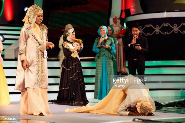 Obabiyah Aishah Aijbola right World Musimah from Nigeria falls to her knees in prayer after being named World Muslimah 2013 the 3rd annual World...
