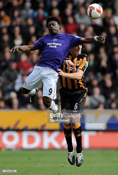 Obafemi Martins of Newcastle United and Michael Turner of Hull City challenge for a header during the Barclays Premier League match between Hull City...