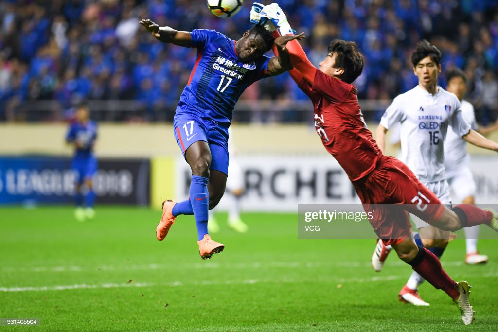 Obafemi Martins #17 of Shanghai Shenhua and goalkeeper No Dong-Geon #21 of Suwon Samsung Bluewings compete for the ball during the 2018 AFC Champions League Group H match between Shanghai Shenhua and Suwon Samsung Bluewings at Hongkou Football Stadium on March 13, 2018 in Shanghai, China.