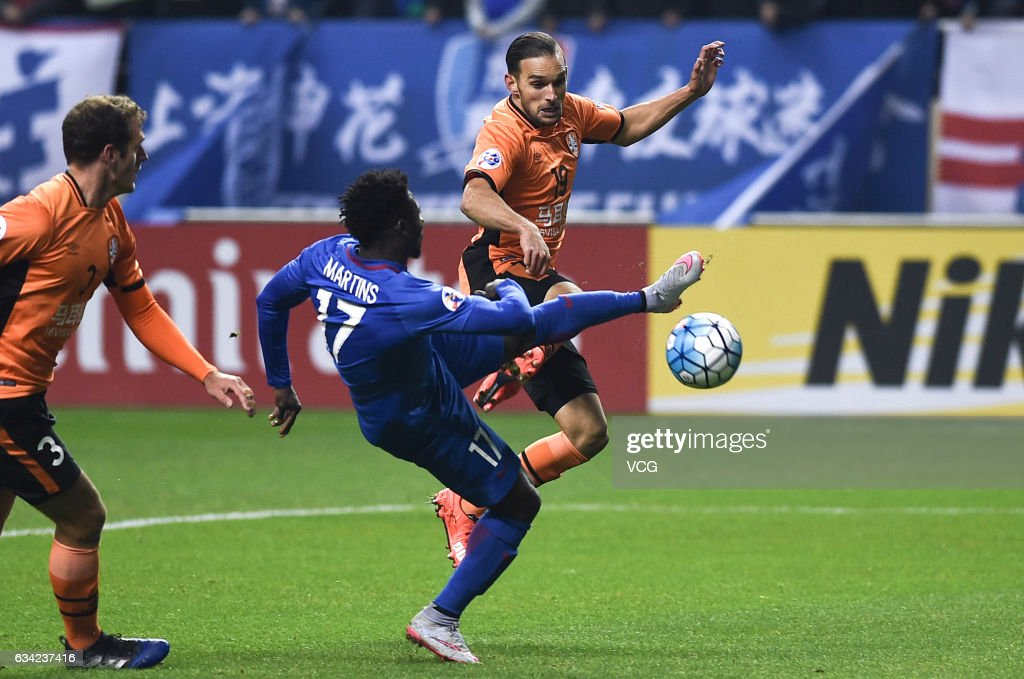 Obafemi Martins #17 of Shanghai Shenhua and Jack Hingert #19 of Brisbane Roar compete for the ball during the AFC Champions League 2017 play-off match between Shanghai Shenhua and Brisbane Roar at Hongkou Stadium on February 8, 2017 in Shanghai, China.