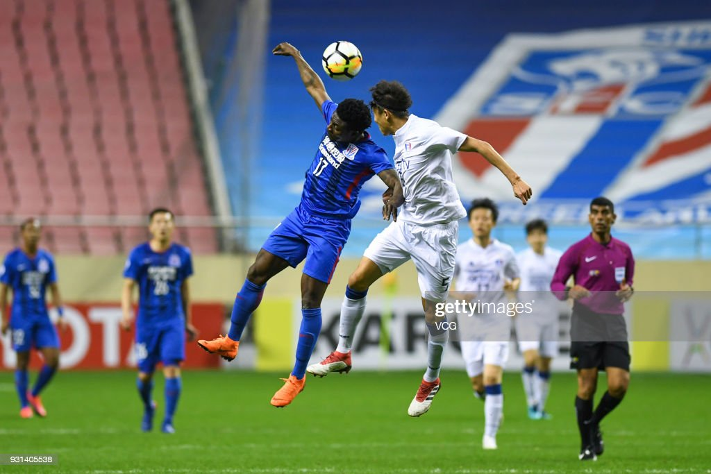 Obafemi Martins #17 of Shanghai Shenhua and Jo Sung-Jin #5 of Suwon Samsung Bluewings compete for the ball during the 2018 AFC Champions League Group H match between Shanghai Shenhua and Suwon Samsung Bluewings at Hongkou Football Stadium on March 13, 2018 in Shanghai, China.