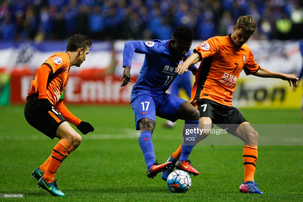 Obafemi Martins #17 of Shanghai Shenhua and Thomas Kristensen #7 of Brisbane Roar compete for the ball during the AFC Champions League 2017 play-off match between Shanghai Shenhua and Brisbane Roar at Hongkou Stadium on February 8, 2017 in Shanghai, China.