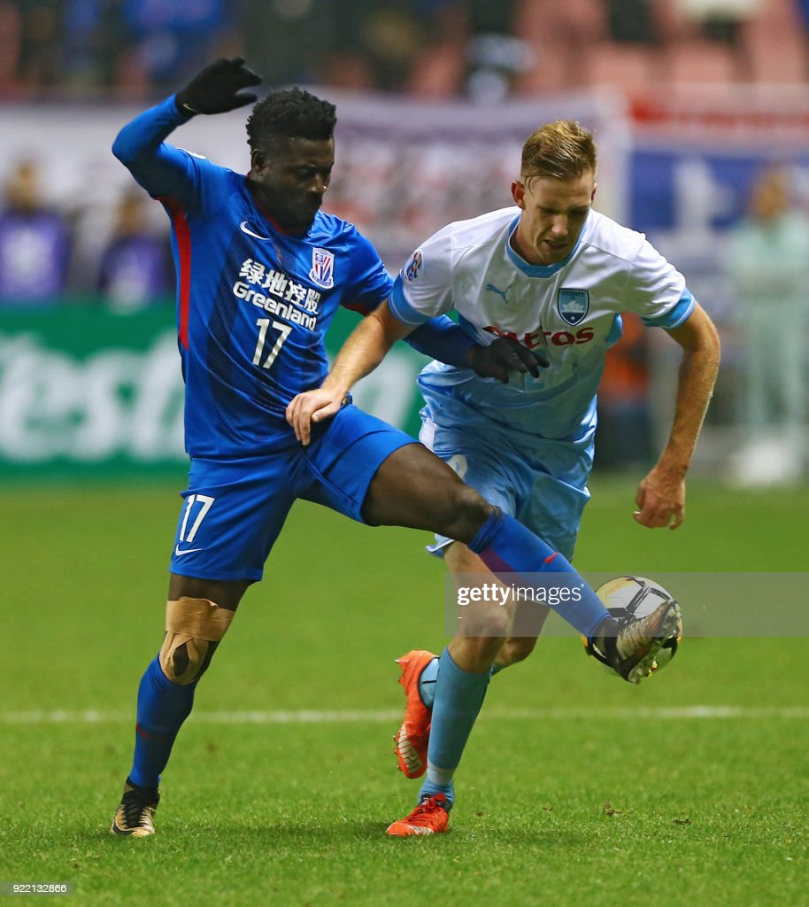 Obafemi Martins (L) of Shanghai Shenhua competes for the ball with Aaron Calver of Sydney FC during their AFC Champions League group stage football match in Shanghai on February 21, 2018. / AFP PHOTO / - / China OUT